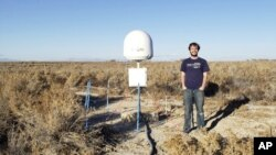 This undated photo provided by Caltech shows radio astronomer Christopher Bochenek with a STARE2 station he developed near the town of Delta, Utah. (Caltech via AP)