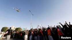 FILE - A military helicopter hovers above as followers of the Houthi movement as they demonstrate to show support to the movement in Sanaa, January 23, 2015.