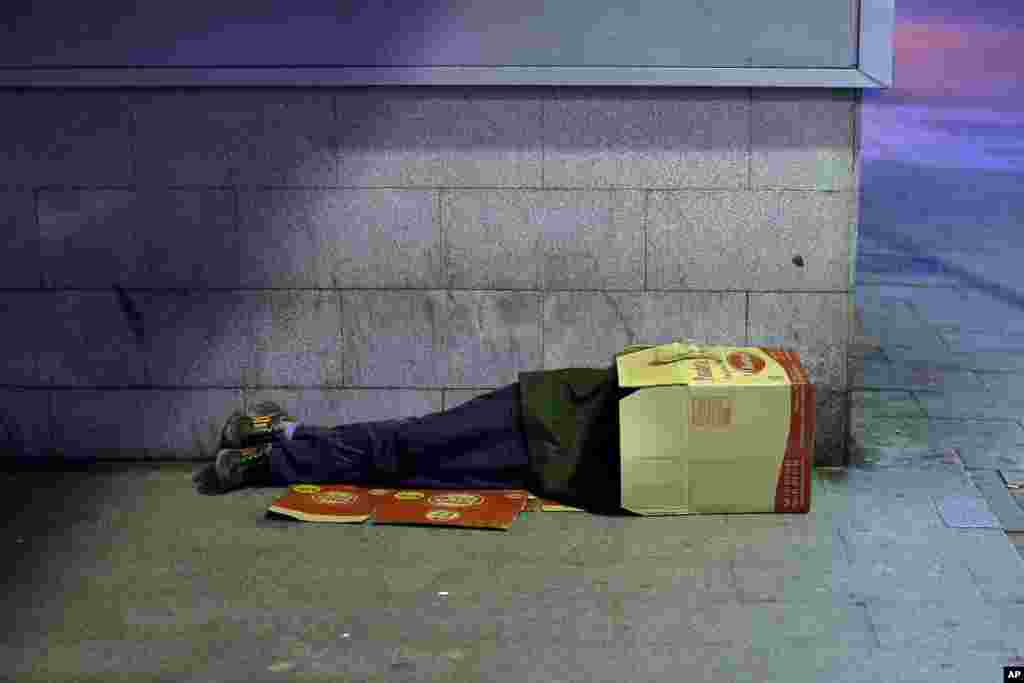 A man sleeps inside a cardboard box in Madrid, Spain. The unemployment rate for the July-September period fell from 26.3 percent to 26.0 percent.