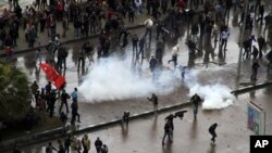 Polisi anti huru-hara Mesir menembakkan gas air mata untuk memisahkan kedua kubu demonstran yang bentrok di Alexandria, Mesir (21/12).