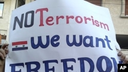 """利比亚抗议者举着""""我们要自由,不要恐怖主义""""的口号"""