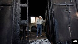FILE - A Palestinian inspects a house after it was torched in a suspected arson attack by Jewish settlers, killing an 18-month-old Palestinian toddler and his parents, in Duma village near the West Bank city of Nablus, July 31, 2015.
