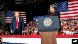 Presiden Donald Trump mendengarkan Sean Hannity dari Fox News berbicara dalam sebuah acara di Show Me Center di Cape Girardeau, 5 November 2018. (Foto: AP)