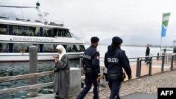 Petugas kepolisian yang sedang berpatroli melintas di depan seorang perempuan yang mengenakan hijab di Zell am See, Austria, 1 Oktober 2017.