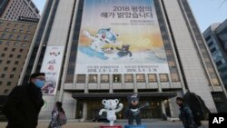 """People pass a banner promoting the upcoming 2018 Pyeongchang Winter Olympic as official mascots, a white tiger 'Soohorang' for the Olympic, and the Asiatic black bear """"Bandabi"""" for the Paralympic (Bottom-R) are displayed in downtown in Seoul, South Korea, Jan. 9, 2018."""