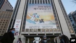 """Para pejalan kaki melewati poster Olimpiade Musim Dingin 2018 Pyeongchang dan maskot olimpiade, macan putih 'Soohorang' dan beruang hitam """"Bandabi"""" untuk paralimpik di pusat Kota Seoul, Korea Selatan, 9 Januari 2018."""