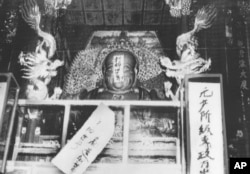 "FILE - In this file photo taken Aug. 27, 1966, a Buddha statue is covered with signs reading ""Destroy the old world,"" and ""Establish a new world,"" by ultra-patriotic Red Guard who reject ancient Chinese traditions at Lin Yin temple in Hangzhou, China."