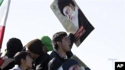 ພວກຊາວໜຸ່ມອີຣ່ານ ພາກັນຮ້ອງຄຳຂວັນແລະຊູຮູບປົສເຕີ້ ຜູ້ນຳສູງສຸດອີຣ່ານ Ayatollah Ali Khamenei ໃນລະຫວ່າງການໂຮມຊຸມນຸມ ສະເຫຼີມສະຫຼອງການປະຕິວັດອິສລາມ ຄົບຮອບ 33 ປີທີ່ນະຄອນຫຼວງເຕຫະຣ່ານ (11 ກຸມພາ 2011)