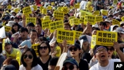 FILE - South Koreans shout slogans during a rally demanding the adoption of a special law for the sunken ferry Sewol in Seoul, South Korea, Friday, Aug. 15, 2014.