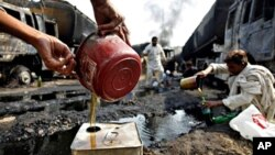 Villagers collect oil leaked from NATO trucks torched by gunmen in Khairabad near Peshawar, Pakistan, 07 Oct. 2010