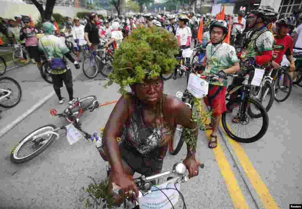 A costumed woman rides her bike during the 15th tour of the fireflies in Pasig city, metro Manila, Philippines. The annual tour of the fireflies advocates clean air and healthy living by promoting bicycles as the main mode of transportation. This year's tour aims to raise funds to benefit to the victims of supertyphoon Haiyan.