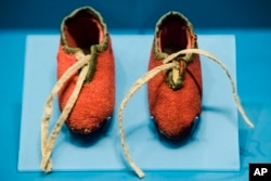Photo shows a newborn's shoes made from a British red coat brought back at the end of the Revolutionary War