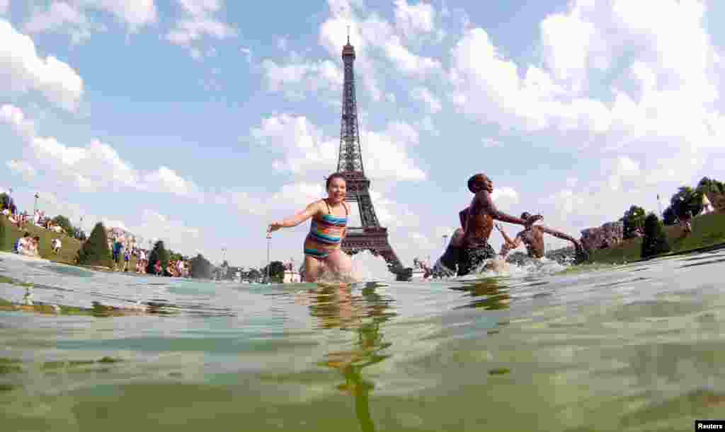 Youth cool off in a fountain of the Trocadero Square in front of the Eiffel Tower on a warm summer afternoon in Paris.