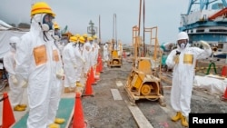 Members of a Fukushima prefecture panel, which monitors safe decommissioning of the nuclear plant, inspect the construction site of the shore barrier at the tsunami-crippled Fukushima Daiichi nuclear power plant in Fukushima, in this photo released by Kyo