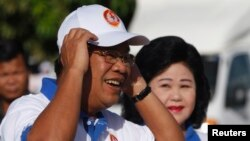 Cambodia's Prime Minister Hun Sen and his wife Bun Rany (R) arrive at an election campaign area in Phnom Penh, June 27, 2013.