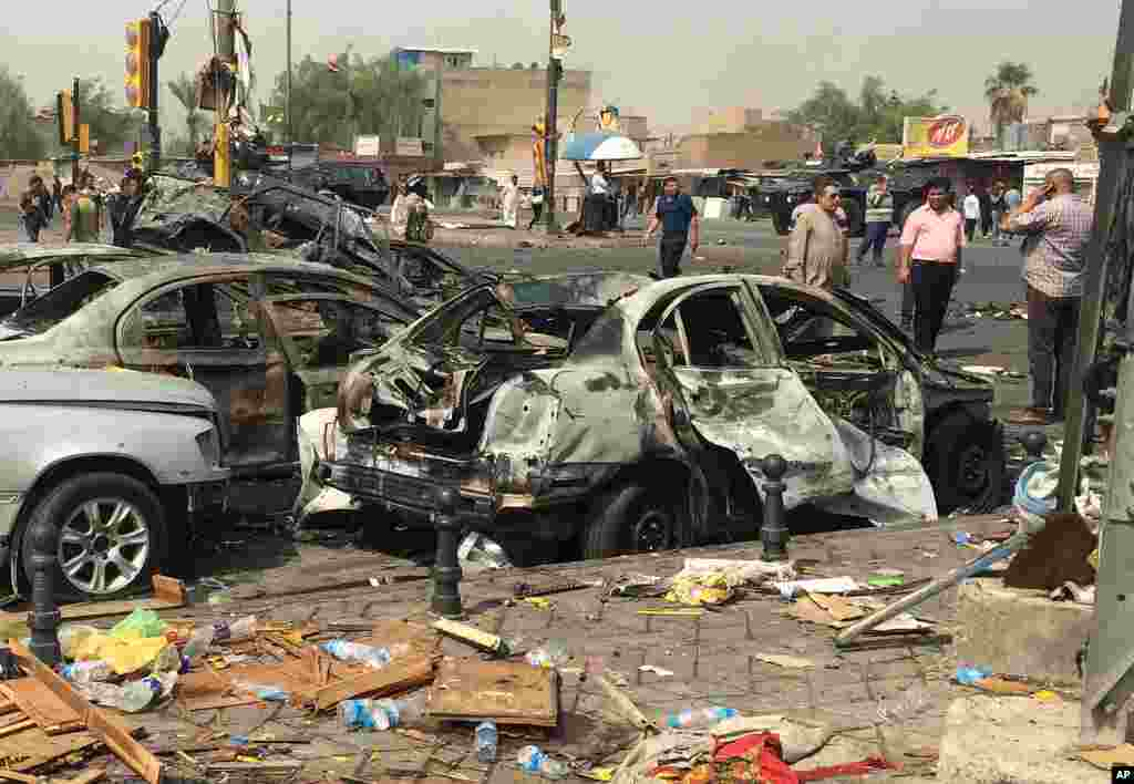 Civilians observe the damage caused by a car bomb in the commercial area of New Baghdad, Iraq, Aug. 26, 2014.