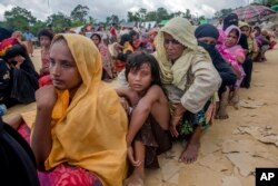 Rohingya Muslims, who recently crossed over from Myanmar into Bangladesh, wait for their turn to receive food aid near Balukhali refugee camp, Bangladesh, Friday, Sept. 15, 2017. Thousands of Rohingya are continuing to stream across the border.