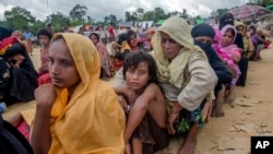Rohingya Muslims, who recently crossed over from Myanmar into Bangladesh, wait for their turn to receive food aid near Balukhali refugee camp, Bangladesh, Friday, Sept. 15, 2017. Thousands of Rohingya are continuing to stream across the border, with U.N. officials and others demanding that Myanmar halt what they describe as a campaign of ethnic cleansing that has driven nearly 400,000 Rohingya to flee in the past three weeks.