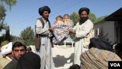 Warga sipil di provinsi Helmand menunjukkan dua anak kecil yang menjadi korban serangan udara NATO (29/5).