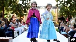 "Young models wear two of 2014's hottest Halloween costumes, (from left) Anna and Elsa from Disney's ""Frozen"" at a Disney Halloween Fashion Show on Oct. 1, 2014, in Glendale, Calif."
