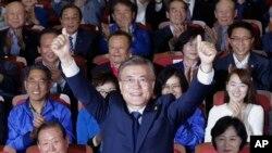 Kandidat presiden Korea Selatan Moon Jae-in dari Partai Demokrat mengangkat tangannya saat para pemimpin partainya serta anggotanya menyaksikan hasil siaran televisi lokal media lokal dalam pemilihan presiden di Seoul, Korea Selatan, Selasa 9 Mei 2017. (AP Photo/Ahn Young-joon)