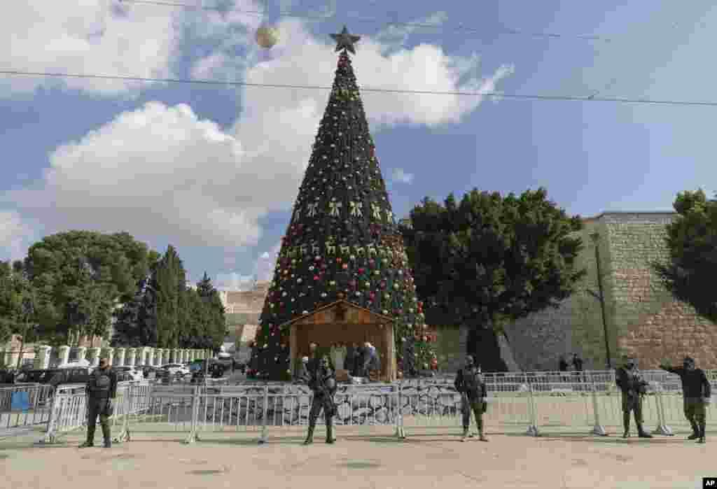 Pasukan keamanan nasional Palestina dikerahkan di Manger Square, berdekatan dengan Gereja Nativitas, yang diyakini oleh umat Kristen sebagai tempat kelahiran Yesus Kristus, menjelang perayaan Natal di kota Betlehem, Tepi Barat, Palestina (Foto: Nasser Nasser/ AP).