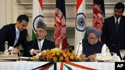 Indian PM Manmohan Singh (R) and Afghanistan President Hamid Karzai, sign agreements during a meeting in New Delhi, Oct. 4, 2011