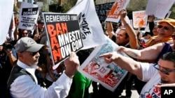 3月11日在亞利桑娜州菲尼克斯舉行的反對遞解出境中,支持移民權利的遊行者指著一名手舉標語牌反移民權利的抗議者(左)叫罵