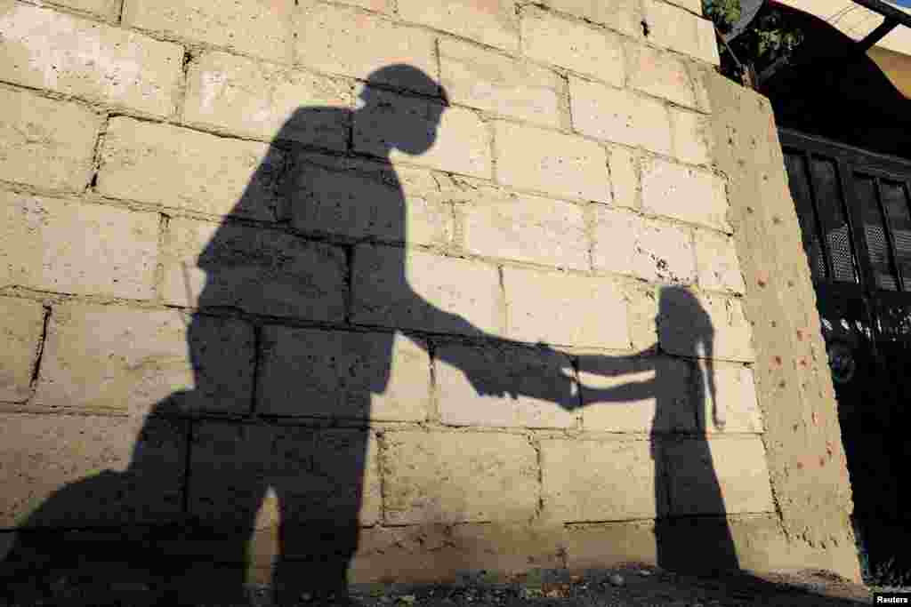 "The shadow of a girl receiving a meal for iftar, or the evening meal, to break fast, from a member of ""Tkiyet Um Ali"" humanitarian services center is cast on a wall in front of her family home in the city of Russeifa, Jordan, during the holy fasting month of Ramadan."