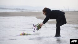FILE - A woman puts flowers into the sea to pray for victims of the 2011 earthquake and tsunami in Sendai, northern Japan on the anniversary of the event. (AFP / TORU YAMANAKA)