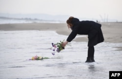 FILE - A woman puts flowers into the sea to pray for victims of the 2011 earthquake and tsunami in Sendai, northern Japan, March 11, 2016.