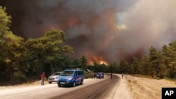 Paramilitary police officers and people watch as a wildfire strengthened by winds spread near the Mediterranean coastal town of Manavgat, Antalya, July 28, 2021. (AP Photo)