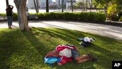 Seorang pria tunawisma tidur di rumput dekat Pantai Waikiki, Honolulu. (Foto: Dok)