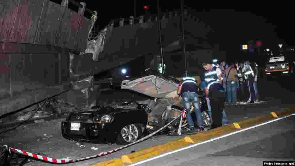 Các thành viên của dịch vụ khẩn cấp Ecuador xem xét một chiếc xe bẹp dúm cạnh chiếu cầu bị sập vì động đất tại thành phố Guayaquil, ngày 16/4/2016.