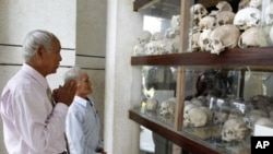 """Survivors of the Khmer Rouge regime, Chum Mey (L) and Bou Meng (C) pray at Choeung Ek """"Killing Fields"""" site located on the outskirts of Phnom Penh, June 25, 2011"""