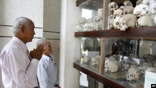 "Survivors of the Khmer Rouge regime, Chum Mey (L) and Bou Meng (C) pray at Choeung Ek ""Killing Fields"" site located on the outskirts of Phnom Penh, June 25, 2011"
