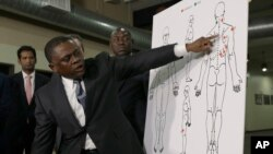 Pathologist, Dr. Bennet Omalu, gestures in front of a diagram showing the gun shot wounds he found on the body of police shooting victim Stephon Clark, during a news conference, March 30, 2018, in Sacramento, California.