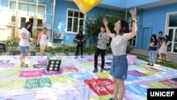 "Young people play an ""HIV knowledge"" board game at an event to promote sexual and reproductive health among adolescents supported by the China Center for Health Education and UNICEF China."