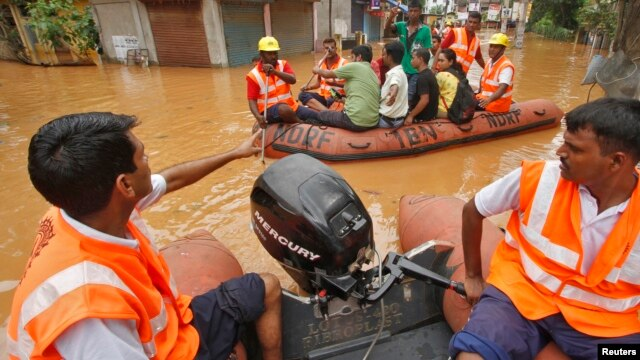 India's National Disaster Response Force personnel use rafts to rescue flood-affected residents after heavy rains at Guwahati in the northeastern Indian state of Assam, June 27, 2014.