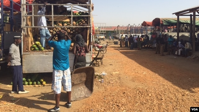 Workers offload fruit trucks from Uganda at Juba's Gumbo Market on March 10, 2015. Business owners are feeling the pressure as the strength of the South Sudanese pound weakens. (Photo: G. Joselow / VOA)