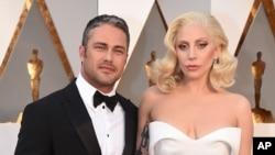 Lady Gaga dan tunangannya, aktor Taylor Kinney, di Dolby Theatre di Los Angeles menjelang acara Academy Awards (28/2). (AP/Invision/Jordan Strauss)