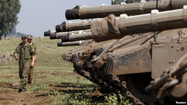 Israeli soldiers walk near tanks close to the ceasefire line between Israel and Syria on the Israeli occupied Golan Heights, May 6, 2013.