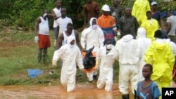 Rescue workers carry the body of a victim from the site of a mudslide in Regent, east of Freetown, Sierra Leone, Aug. 14, 2017.