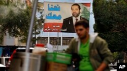 A street vendor stands in front of a poster of outgoing Prime Minister Saad Hariri that hangs on a street in Beirut, Lebanon, Nov. 6, 2017.