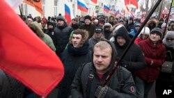 Les Russes, avec des drapeaux de différents mouvements d'opposition, marchent à la mémoire du chef de l'opposition Boris Nemtsov à Moscou, en Russie, le dimanche 25 février 2018.
