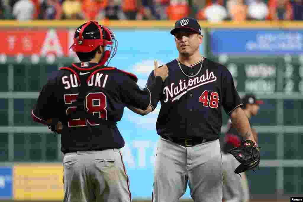 El catcher de los Nacionales de W., Kurt Suzuki (28) saluda al lanzador Javi Guerra al concluir el 2do partido ganado alos Astros el 23 de octubre de 2019. Reuters.