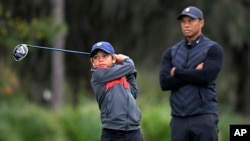 FILE - Tiger Woods, right, watches as his son Charlie tees off during a practice round of the Father-Son Challenge golf tournament, Dec. 17, 2020, in Orlando, Fla. (AP Photo/Phelan M. Ebenhack)