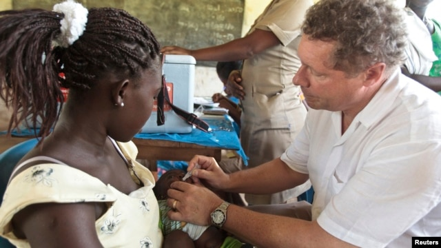 FILE - GAVI chief Seth Berkley inoculates a child with a Rotavirus vaccine at the in the village of Nkyenoa, Ghana, April 27, 2012.