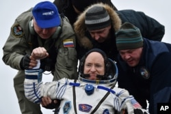 FILE - Ground personnel help International Space Station (ISS) crew member Scott Kelly of the U.S. to get off the Soyuz TMA-18M space capsule after landing near the town of Dzhezkazgan, Kazakhstan on March 2, 2016.