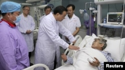 Chinese Premier Li Keqiang, third from right, talks with an injured woman as he visits survivors of a ship that sank at the Jianli section of the Yangtze River, at a hospital in Jianli, Wuhan province, China, June 2, 2015.